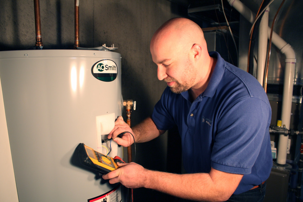 A plumber checking an electric water heater with a multi-meter.