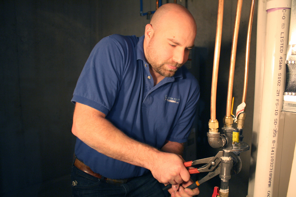 A plumber tightening gas pipe fittings.