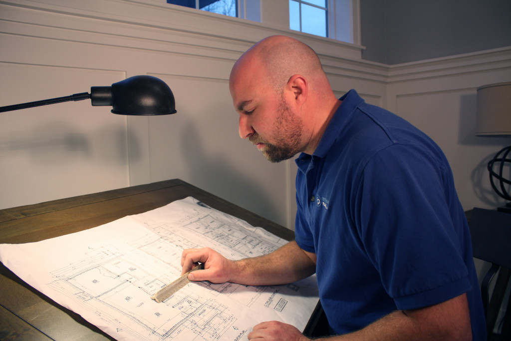 A plumber studying architectural blueprints.