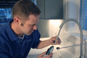 A plumber assembling a kitchen faucet