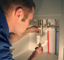 A plumber installing a P-trap in a bathroom vanity sink.